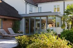 A modern kitchen extension with structurally glazed wrap around windows and bifold aluminium doors.