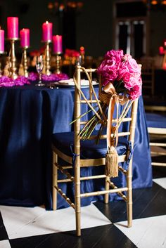 Gold tassels and hot pink flowers as chair decor.