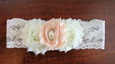This beautiful handcrafted baby headband features three shabby roses in ivory and peach with exquisite pearl and rhinestone embellishment.
