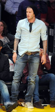 Beckham shows off his sartorial taste on the sidelines. Rolled up shirt sleeve and jeans.