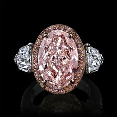 6.77 carat oval fancy pink diamond with shield cut accent stones