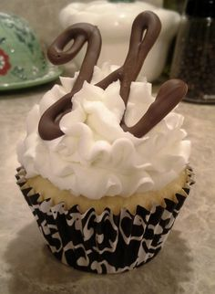 Cupcakes with Chocolate Monogram....melt chocolate and use a frosting tip to squeeze it on wax paper, put it in the freezer, when chocolate is frozen peel off chocolate design and place on cupcake. Keep refrigerated till ready to give out.