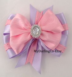 This Bow is Disney Inspired, Princess Rapunzel from the Movie Tangled.    Lavender Satin with Pink Moire Ribbon featuring a Beautiful Rhinestone