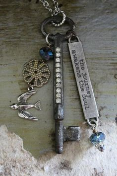 "A wonderfully inspiring necklace. A silver chain, ~34"" in length, has a vintage silver key with clear rhinestones down the shaft. The key hangs another ~3.5"". ""The journey awakens the soul"" is stamped on a plate that dangles from the key. On the opposite side dangles a smoky teal crystal bead, a flower and a bird in flight."