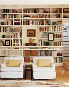 Elegant Arrangement These floor-to-ceiling bookcases are original to the house and hold various family objects such as woven baskets to keep family photos, book collections, and a display area.