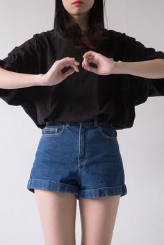 over sized black long sleeve tucked into blue high waisted shorts