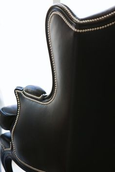 Nickel nail heads line the carved high gloss black frame of our leather wing chair. Screams handsome/bold/chic!