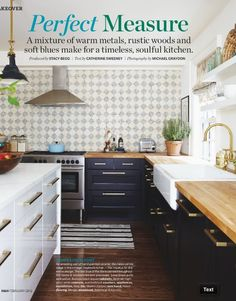 Gold hardware on dark blue and gray cabinets, light butcher block countertops