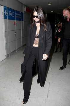Kendall Jenner wears a long black coat, lace bralette, black pants, rectangular sunglasses, and sandals