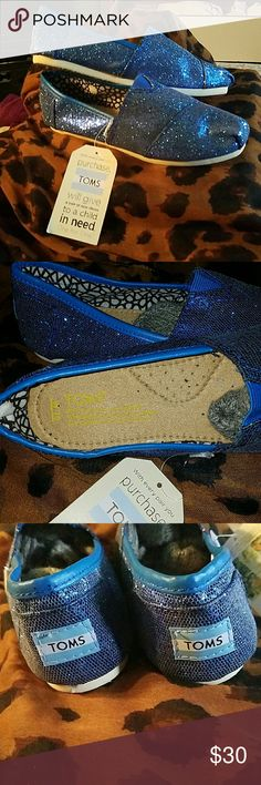 """Sparkly Blue TOMS The perfect and effortless casual, running around slip-on shoe. I purchased a bunch of these on a whim online without paying attention to the description.  Inside says W10 (woman size 10) but also Euro 40 which technically is a US 9 womens, needless to say they do fit more like a 9-9.5. I'm a true size 10 and if I struggle and cry I can get my big foot in there but they fit snug.  Anywho my impulsive behavior is your style opportunity. Measures 10"""" across bottom sole TOMS…"""