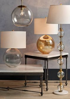 The impressive profile of each striking lamp is thanks to the mouth-blown glass sphere that makes up the body and a classic ivory linen shade. A shiny pipe adds to the visual appeal.
