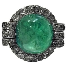 Art Deco Emerald Diamond Platinum Ring, circa 1930. The ring set in the centre with a cabochon light to medium tone bluish-green Emerald, SI1 (type 111 clarity), good transparency, gauging approximately 11.7 x 10.3 x 9.6 mm, approximately 5 carats, the surround art deco basket scroll mount set with 30 mixed old cut diamonds, total diamond weight approximately 1.00 ct