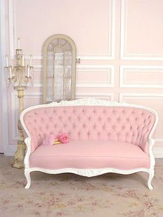 ... lounge on pink and white sofas next to gold candelabra