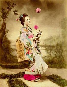 """Studio photograph of a smiling Geisha as juggler. Note: """"Smiling Geisha"""" and """"smiling Maiko"""" photos from the Meiji era are quite rare."""