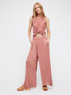 Got Me Twisted Jumpsuit   This wide leg jumpsuit is featured in a soft fabric with tonal stiped.    * Cutout at the midriff with a knot detail   * Open back with adjustable ties   * Elastic waistband   * Hip pockets