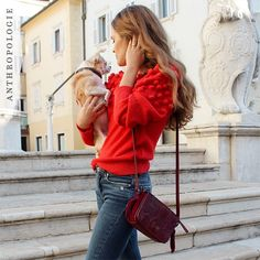 A Girl Called Scarlet in her pom sweater and crossbody bag | Shop Anthropologie