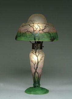 Spectacular Daum cameo lamp is decorated with famous Daum Rain Scene on shade and base. Cameo and enameled trees are set against a frosted background with a band of rich pink encircling the middle of the shade as well as the middle of the base. Antique art glass lamp.