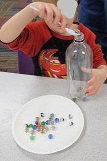 Spoon marbles into a plastic bottle with out using fingers!