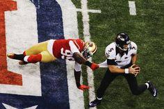 Joe Flacco (5) narrowly escapes the pressure of Aldon Smith (99) during Super Bowl XLVII - Feb 3, 2013