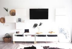 Monochrome Ikea Besta TV wall unit hack - The 3 hanging cupboards beside the TV are for storage & the tops hold art! Brilliant!!   TOMFO