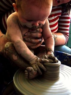 baby at potter's wheel