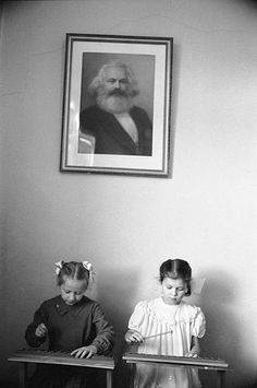 Two girls playing xylophones at a Moscow kindergarten Soviet Union December 1960 Behind them is a portrait of Karl Marx