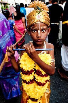 A young boy dressed as the Hindu deity Krishna