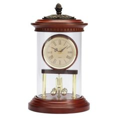 Oval Anniversary Clock - Antique Mahogany - Elegant and classic. The exclusive antique mahogany anniversary clock is the one to give–or display as your own. Set inside a glass dome supported by metal standards, topped with raised resin leaves and finial. Features a quartz movement and swept second hand.