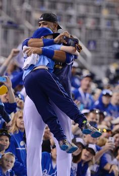 Kansas City Royals catcher Salvador Perez celebrated with a young fan after winning the playoff baseball game against Baltimore Orioles on Wednesday October 15, 2014 at Kauffman Stadium in Kansas City, MO. The Royals beat the Baltimore Orioles 2-1 to win the ALCS.