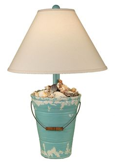 "Enjoy this 27.5"""" Bucket of Shells Turquoise beach cottage lamp! Created with a soft distressed turquoise and off-white finish, complete with real seashells decorating the top of the lamp base and met"