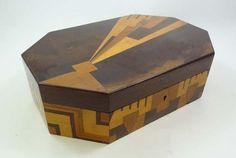 "An Art Deco parquetry jewellery box of rectangular shape w/ canted corners, decorated w/ geometric design of the genre, the cover lifting to reveal fitted lift-out tray w/ further storage beneath. Length 11"" (hva)"