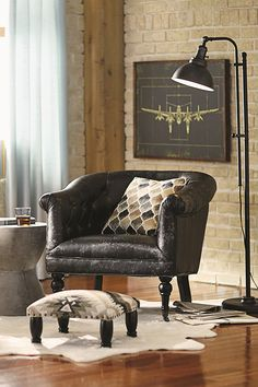 The industrial style exposed brick walls, black leather accent chair, and southwestern accents give this living room a chic rustic look.