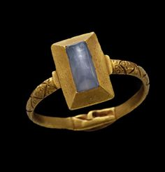 """terminating at strengthened shoulders supporting the oblong """"pie-dish"""" bezel set with a cabochon sapphire. At the base of the hoop there is a fede, or pair of hands clasped in love and friendship. English, 13th century."""