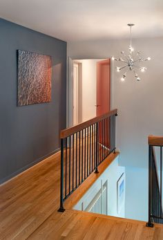 This hallway includes hardwood flooring, a dark gray accent wall and black metal. This hallway includes hardwood flooring, a dark gray accent wall and black metal railing topped with wood. A sputnik chandelier illuminates the space. Black Stair Railing, Wrought Iron Stair Railing, Metal Railings, Black Stairs, Metal Stairs, Railings For Stairs, Open Stairs, Flooring For Stairs, Hardwood Stairs