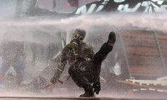 A protestor hit by police water cannon falls during clashes in Taksim Square in Istanbul on June 11, 2013. (Kerim Okten/EPA) #