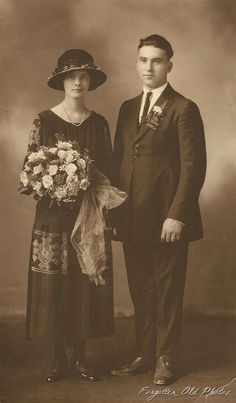Circa 1920s. Might this be a foreign photo?  The cut of his suit is different, with three buttons right in front and what looks to be darts or a gathering on the side of the suit coat.  He is also wearing a thin tie.  The bride is wearing a beautiful dark dress with light colored embroidery, with a large hat, large bouquet, and a single strand of pearls.  She is also wearing what appears to be patent leather shoes.