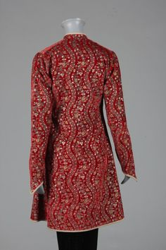 Mariano Fortuny stencilled red velvet jacket, circa 1920-30, the rich deep red velvet stencilled with undulating foliate stripes in gold and silver, the jacket of long slim-fitting oriental shape, with pointed, curved cuffs, piped in grey silk and lined in grey satin, fastened by striped grey glass beads