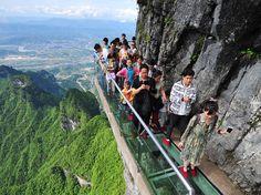 Cuadro de turistas en una pasarela de cristal en la montaña Tianmen en Zhangjiajie, China