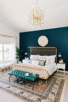 a modern boho master bedroom with dark teal, copper and white colors.