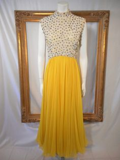 This is an evening gown with a yellow chiffon skirt and a bodice covered with white fabric flowers, white glass beads, clear glass beads with silver