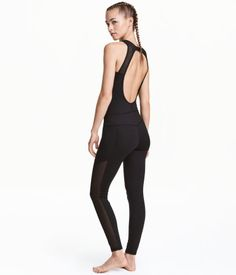 Black. Sleeveless, fitted jumpsuit in fast-drying functional fabric with mesh details, opening at back of neck with plastic fastener, and long legs.