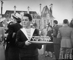French sailor serving cocktails at an officers' party, 1951, photo by Nat Farbman