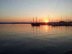 vele, imbarcazioni e colori del tramonto con il Sole che illanguidisce sul mare liscio come l'olio del porto Grande a Siracusa