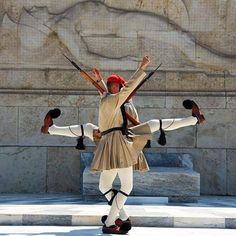 Greek presidential guards (Evzones) perform ceremonial duties at the monument of the Unknown Soldier in front of the Greek Parliament in Athens