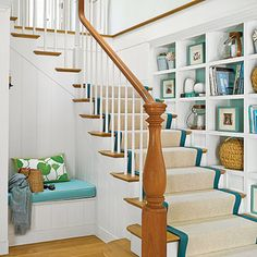 Tucked into the wall along a staircase, this clever shelf space makes use of an often under-used area. The square shelf units mimic the stairs, and the backs are painted a seaglass hue, in keeping with the home's palette of turquoise, green, navy, and white.