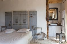 Dans une chambre, des vieux volets font office de tête de lit, des chaises de jardin sont détournées en chevets