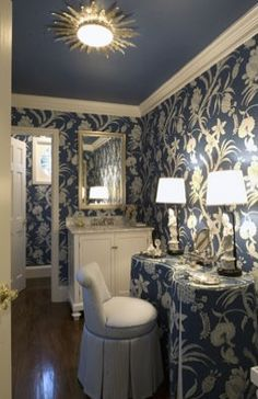 Love this blue and white dressing room with its feminine  skirted vanity in the same pattern as the pretty wallpaper. I also like the way they carried the background color up to the ceiling.
