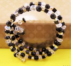 """This """"Bejeweled"""" Wrap Bracelet is strung on stainless steel memory wire and it wraps around your wrist three times in Black Onyx, Iridescent Crystals, Lt. Yellow Seed Beads"""