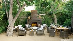 Tobin completely revamped the backyard. She used brick from an old patio for the new fireplace and created a terrace from sand mixed with granite. A candlelit chandelier can be raised and lowered by a rope pulley rigged to a tree. It casts a soft glow over Restoration Hardware's Gun Barrel Salvaged Wood dining table and all-weather wicker from World Market.   - HouseBeautiful.com