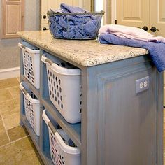 To keep large and unattractive laundry baskets off the floor, this homeowner custom-designed shelving inside the island in the laundry room. The functional baskets are used to separate laundry loads. The storage island also doubles as a folding area for clothes coming right out of the dryer.